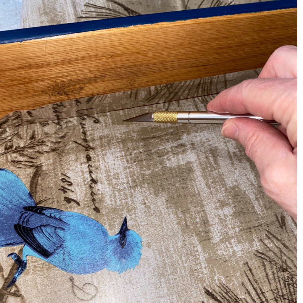 Trimming the Peel and Stick Wallpaper Lined Drawers Using an Exacto Knife